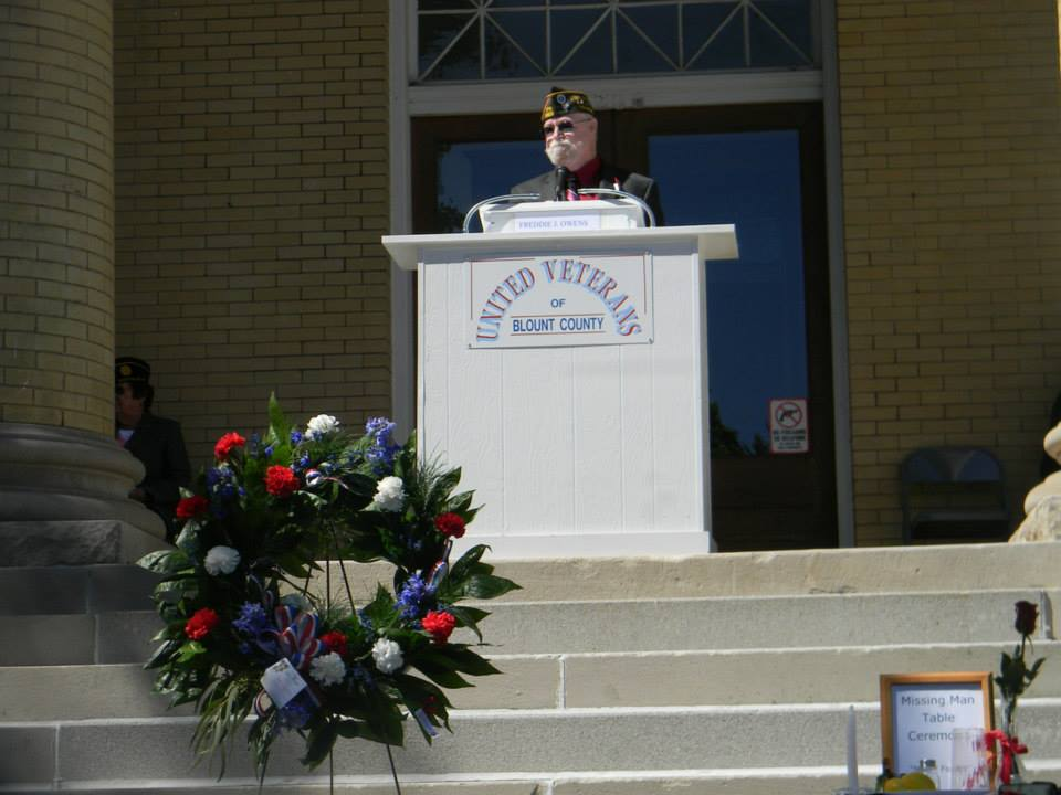 Image of speaker at podium at top of steps of Court House